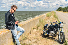 Stylish guy standing next to his motorcycle Stock Images