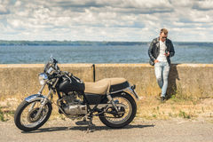 Stylish guy standing next to his motorcycle Stock Image