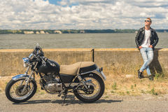Stylish guy standing next to his motorcycle Royalty Free Stock Images