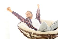 Stylish guy stretching in a comfortable chair. Photo in the background Stock Photography