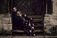 Stylish gypsy couple in love posing in evening city street at old building. woman and man embracing, romantic french atmospheric. Stylish gypsy couple in love royalty free stock photography