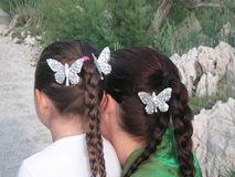 Stylish hair. A little girl and her mum having silver butterflies in the hair.  Photo taken im Makarska, a summer holiday resort in Croatia Royalty Free Stock Images