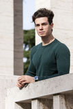 Stylish hair young man outdoors on the ledge, tight knit Royalty Free Stock Photo