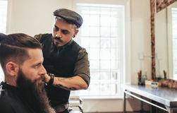 Stylish hairdresser serving client at his shop stock photography