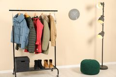 Stylish hallway interior with clothes. On hanger stand royalty free stock photo