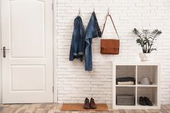Stylish hallway interior with door, comfortable furniture and clothes on wall. Stylish hallway interior with door, comfortable furniture and clothes on brick royalty free stock photos