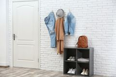 Stylish hallway interior with door, shoe rack and clothes hanging on wall. Stylish hallway interior with door, shoe rack and clothes hanging on brick wall royalty free stock photo