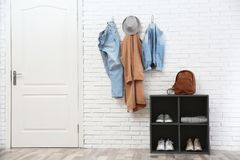 Stylish hallway interior with door, shoe rack and clothes. Hanging on brick wall royalty free stock images