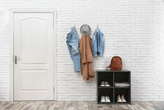 Stylish hallway interior with door, shoe rack and clothes hanging on wall. Stylish hallway interior with door, shoe rack and clothes hanging on brick wall stock images