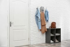 Stylish hallway interior with door, shoe rack and clothes hanging on wall. Stylish hallway interior with door, shoe rack and clothes hanging on brick wall royalty free stock photos
