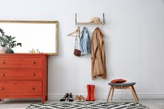 Stylish hallway interior with mirror and chest. Of drawers stock images