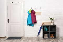 Stylish hallway interior with shoe rack and hanging clothes. On brick wall royalty free stock photo