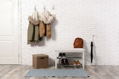 Stylish hallway interior with shoe rack and hanging clothes. On brick wall royalty free stock photos