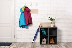 Stylish hallway interior with shoe rack and hanging clothes. On brick wall stock photos