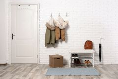Stylish hallway interior with shoe rack and hanging clothes. On brick wall stock images