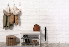 Stylish hallway interior with shoe rack and hanging clothes. On brick wall stock photo