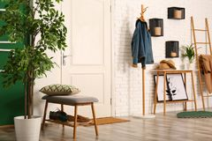 Stylish hallway interior with shoe storage bench and clothes. On hanger stand royalty free stock photo
