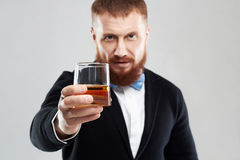 Stylish handsome bearded man offers whiskey Royalty Free Stock Image