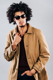 Stylish and handsome. Confident young African man in sunglasses looking away and adjusting his coat while standing against grey background Stock Photos