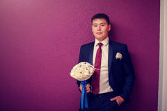 Stylish handsome dark haired groom holding a wedding bouquet in hands standing in purple interior Stock Photo