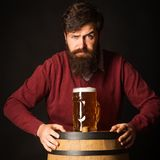 Stylish handsome man drinking beer over Black background. Brewer. Emotional funny bearded drunk hipster holds craft stock image