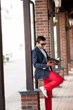 Stylish handsome man reading a magazine on walks. Royalty Free Stock Images