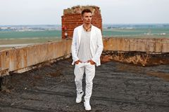 Stylish handsome man in a white T-shirt, jeans and shoes walking. On the roof Stock Photos