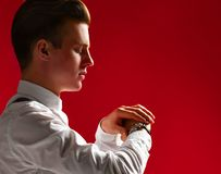 Stylish handsome young Looks at the clock at what time stock images