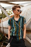 Stylish handsome young male model with sunglasses. In a fashionable shirt with shorts with a bag on the beach near a metal vintage container Royalty Free Stock Photo