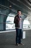 Stylish handsome young male traveller with bristle standing outdoors near the airport terminal. Man wearing jacket and Royalty Free Stock Photography