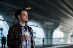 Stylish handsome young male traveller with bristle standing outdoors near the airport terminal. Man wearing jacket and. Shirt. Smiling person looking to camera Royalty Free Stock Photo