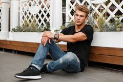 Stylish handsome young man in black T-shirt with jeans. And shoes sitting on the beach stock images