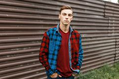 Stylish handsome young man in a fashionable red t-shirt in a trendy plaid multi-colored shirt in blue jeans outdoors. Near a vintage metal fence. Attractive royalty free stock images