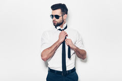Stylish handsome. Stylish young man in white shirt adjusting his necktie and looking away while standing against white background Royalty Free Stock Image