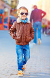Stylish happy boy walking the crowded street Stock Photo