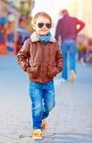 Stylish happy boy walking the crowded street stock photo