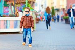 Stylish happy boy walking the crowded street stock photography