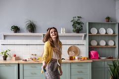 Stylish happy brunette girl in snake printed trousers dancing in the kitchen. royalty free stock photography