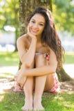 Stylish happy brunette sitting under a tree Royalty Free Stock Photos