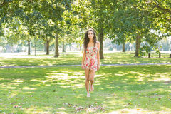 Stylish happy brunette walking on grass Royalty Free Stock Photography
