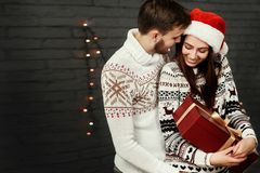Stylish happy couple with big red present smiling gently hugging. At christmas lights. joyful cozy moments in winter holidays. seasonal greetings. advertising Royalty Free Stock Image