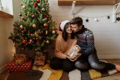 Free Stylish Happy Couple Exchanging Christmas Gifts Under Christmas Tree With Lights. Young Family Hugging And Holding Present, Happy Stock Photography - 192627712
