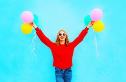 Stylish happy girl with a colorful air balloons is having fun. On blue background Stock Photo