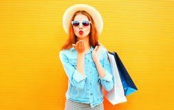 Stylish happy girl sends an air kiss holds a shopping bags Stock Images