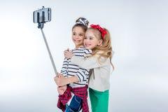 Stylish happy girls making selfie on grey Stock Photography