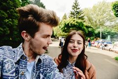 Stylish happy hipster couple having fun laughing and taking self. Ies in the park in town in sunny spring time Stock Image