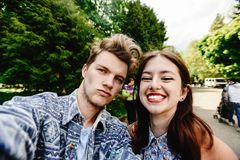 Stylish happy hipster couple having fun laughing and taking self. Ies in the park in town in sunny spring time Royalty Free Stock Photo