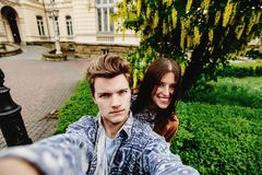 Stylish happy hipster couple having fun traveling and taking selfies in the old city in europe in sunny spring time royalty free stock photos