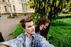 Stylish happy hipster couple having fun traveling and taking selfies in the old city in europe in sunny spring time royalty free stock photo