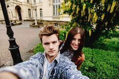 Stylish happy hipster couple having fun traveling and taking selfies in the old city in europe in sunny spring time royalty free stock photography